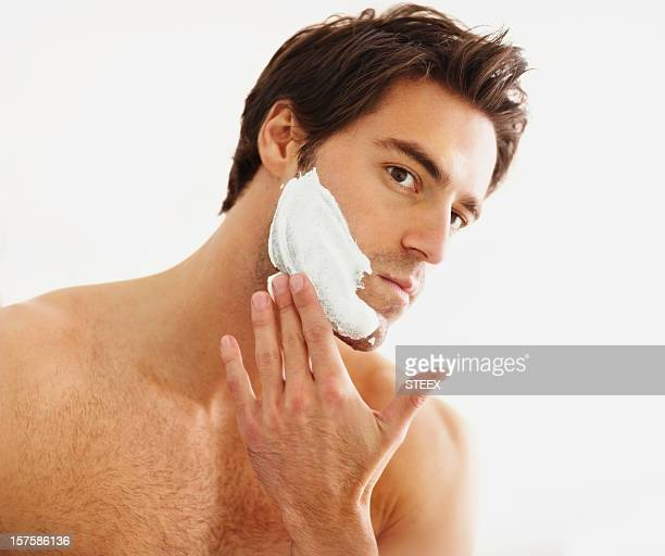 Smart young man applying shaving cream to his face