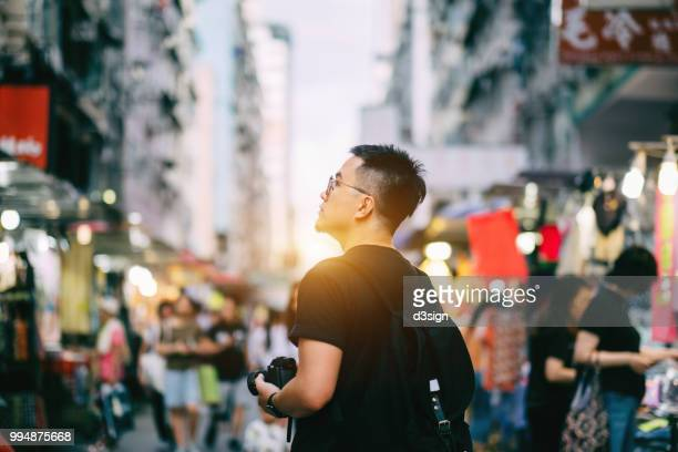 Smart young man carrying camera sightseeing in Hong Kong, exploring busy local night market