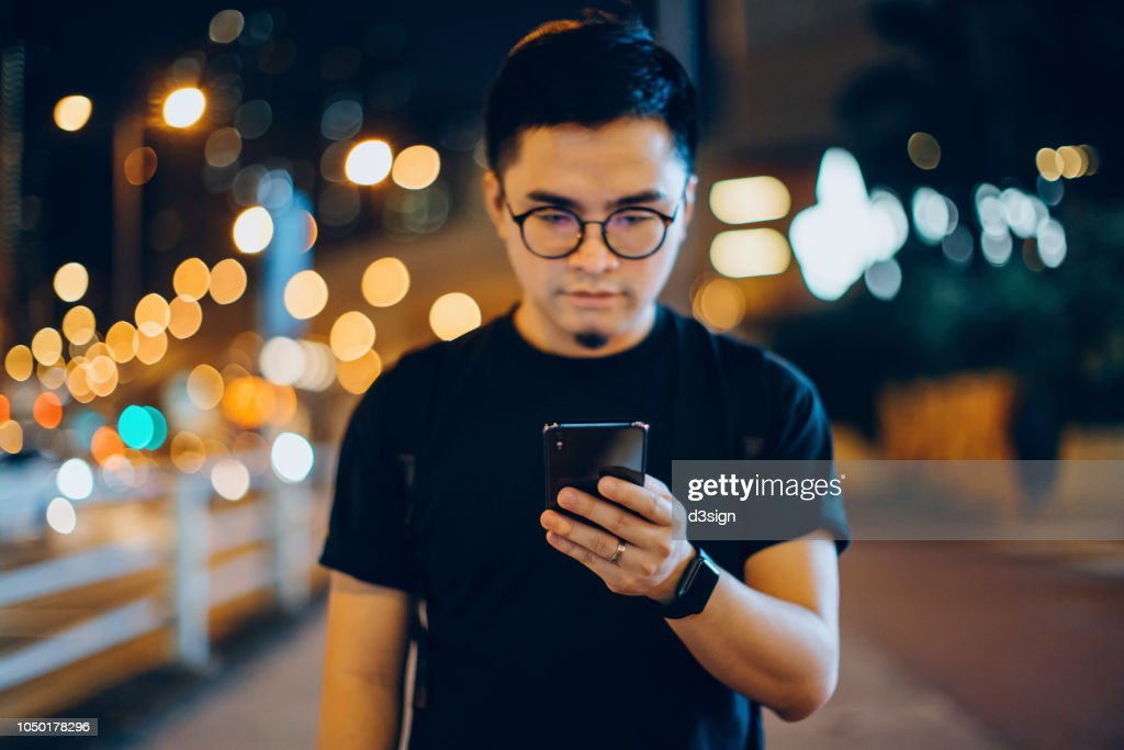 Smart young man text messaging on mobile phone while walking along in city street at night : 圖庫照片