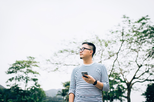 Smart young man using mobile phone while strolling and relaxing in park - gettyimageskorea