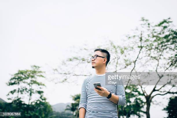 smart young man using mobile phone while strolling and relaxing in park - smart stock pictures, royalty-free photos & images