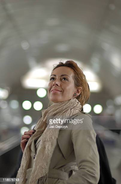 smart young woman rising on escalator, low angle v - depczyk stock pictures, royalty-free photos & images