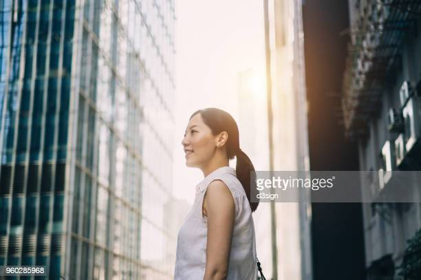 Smart young woman surrounded by highrise corporate buildings and looking up into the sky with confidence