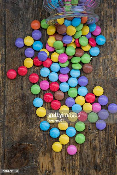 Smarties and candy jar on wood