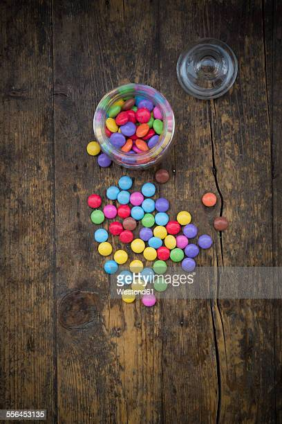 Smarties, candy jar and glass cover on wood
