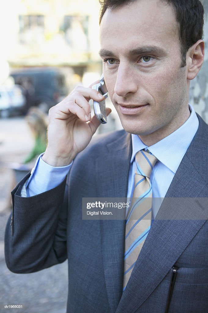 Smartly Dressed Businessman Talks on His Mobile Phone : Stock Photo