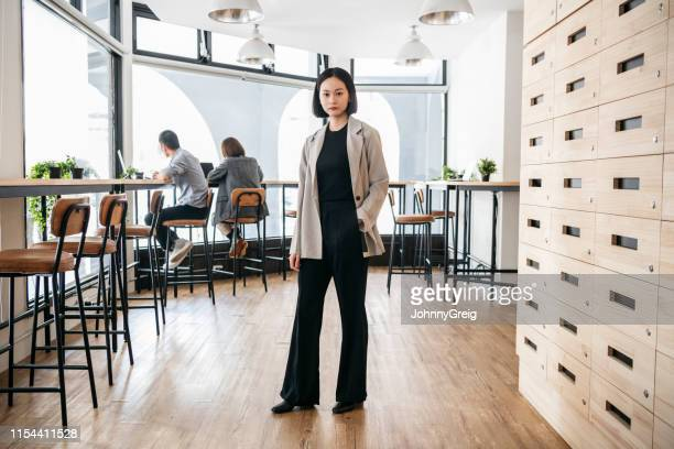 smartly dressed businesswoman in open plan office - incidental people stock pictures, royalty-free photos & images