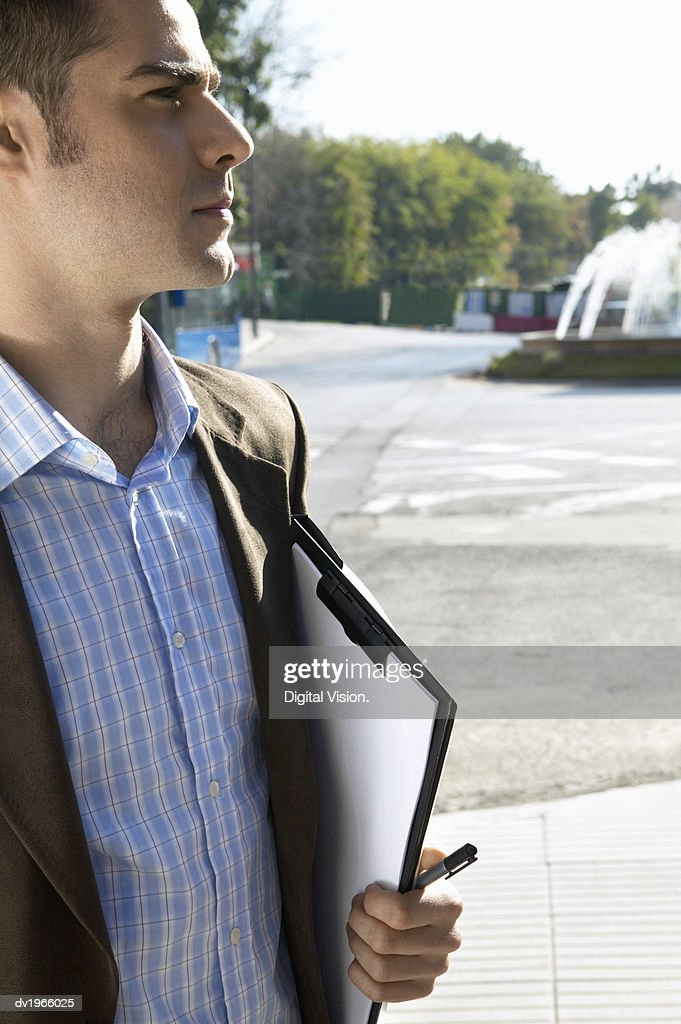 Smartly Dressed Man Holding a Clipboard, Standing in an Urban Setting : Stock Photo