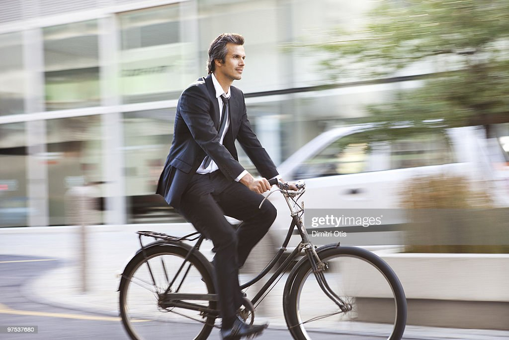 Smartly dressed man riding a bicycle : Stock Photo