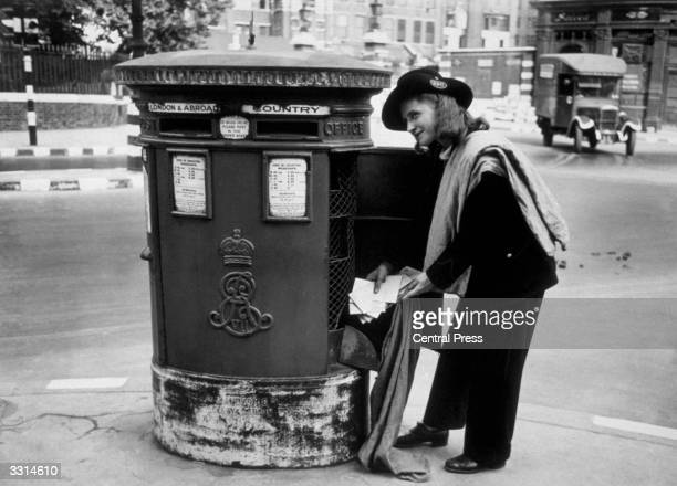 Smartly dressed postgirl makes a collection of mail from a London postbox during World War II.