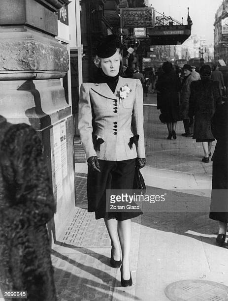 A smartly dressed woman walks down a London street Her tailored suit has squared shoulders and the contrasting buttons and trim on her jacket match...