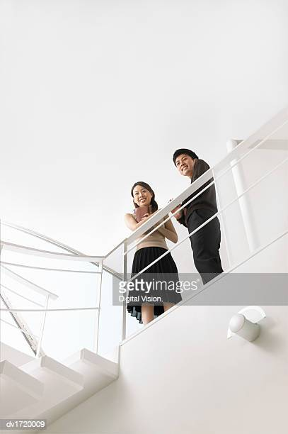 Smartly-Dressed Man and Woman Stand at the Top of a Stairway