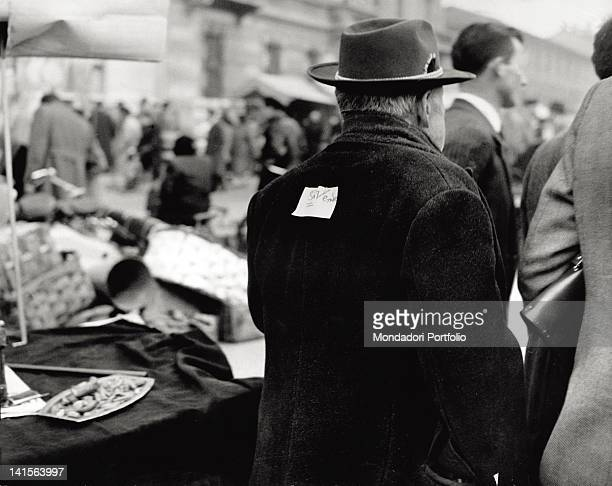 A smartlydressed man in the crowd of the Milanese Fiera di Sinigallia has a funny card stuck on his coat saying 'on sale' Milan November 1955