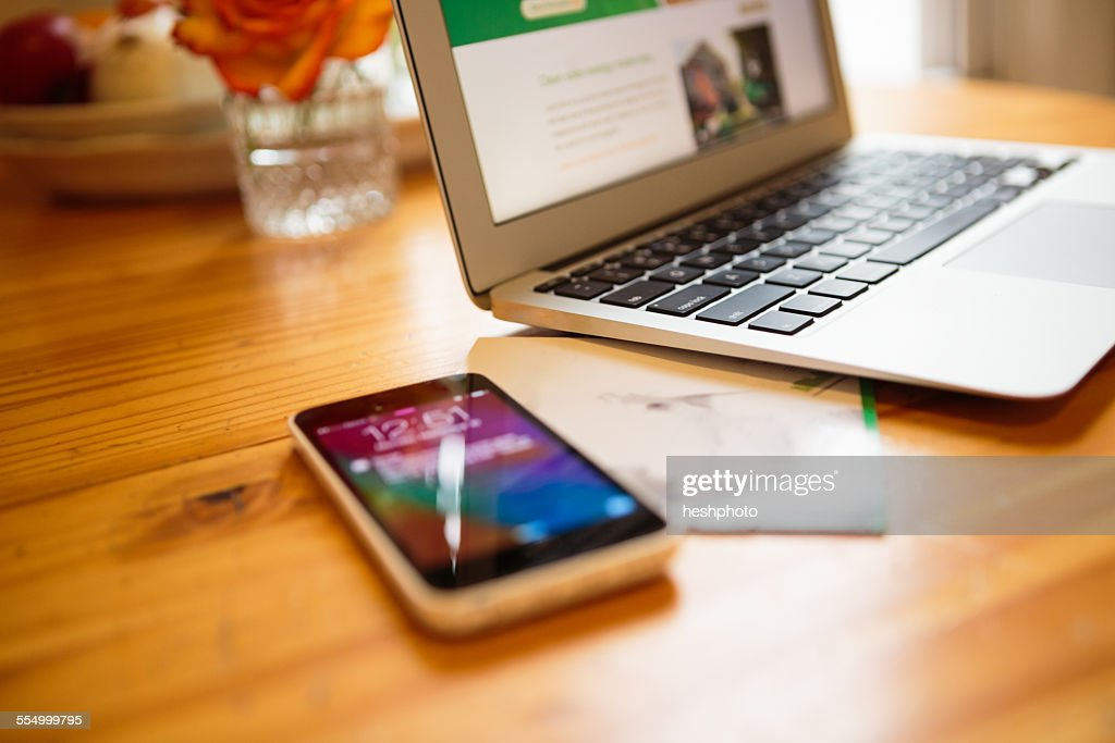 Smartphone and laptop on kitchen table : Stock Photo