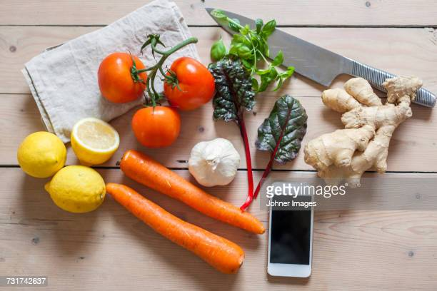 Smartphone and vegetables on table