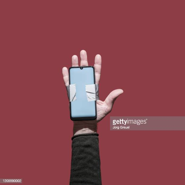smartphone attached to a hand with duct tape - long sleeved stock pictures, royalty-free photos & images