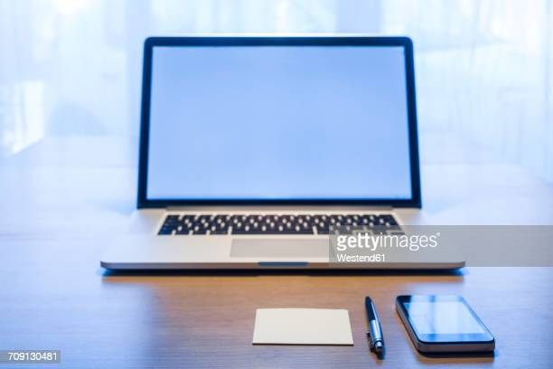 Smartphone, ballpen, adhesive note and laptop on desk