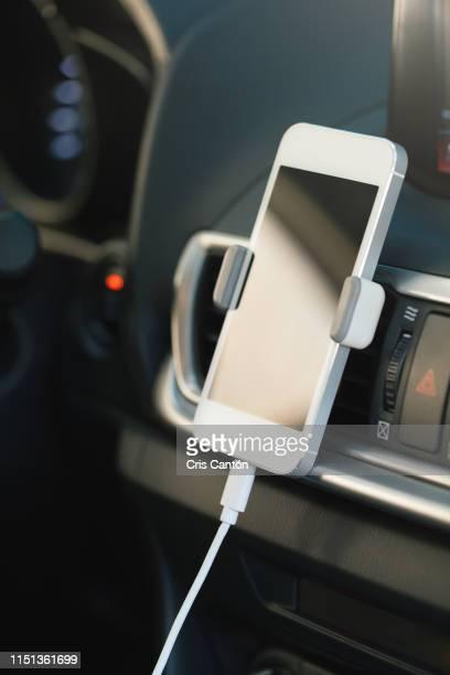 smartphone charging in car - cris cantón photography fotografías e imágenes de stock
