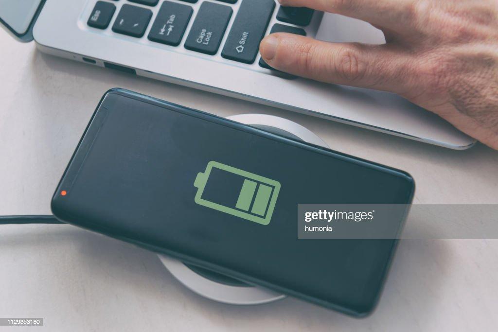 Smartphone auf ein drahtloses Ladegerät aufladen : Stock-Foto