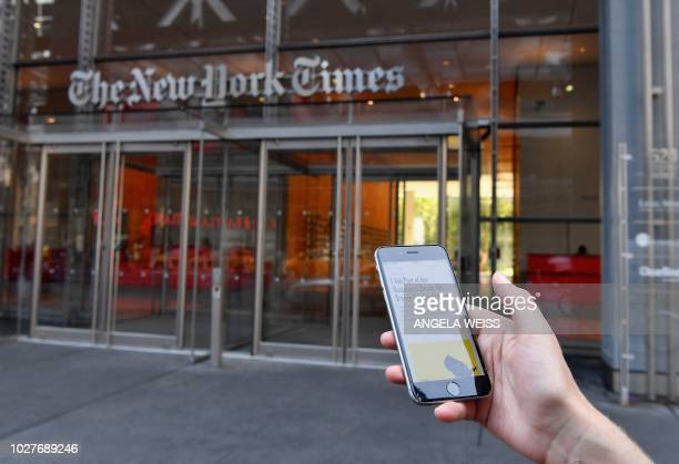 TOPSHOT A smartphone displaying a New York Times opinion piece titled I Am Part of the Resistance Inside the Trump Administration is held up in this...
