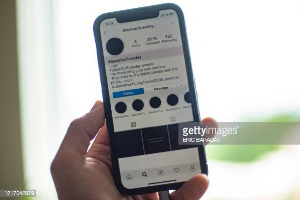 A smartphone displaying the Instagram #blackouttuesday account is seen in Washington on June 2 2020 A work stoppage campaign started by the music...