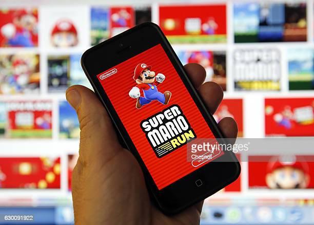 A smartphone displays the start screen of 'Super Mario Run' a sidescrolling adventure game featuring Nintendo Co's Mario popular Italian mascot on...
