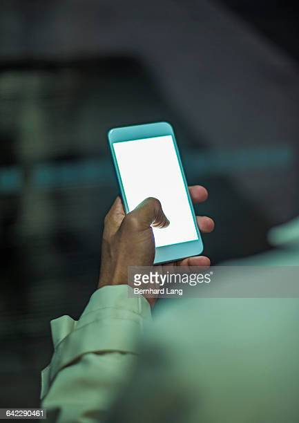 smartphone held by man at night in city, close up - black hand holding phone stock pictures, royalty-free photos & images