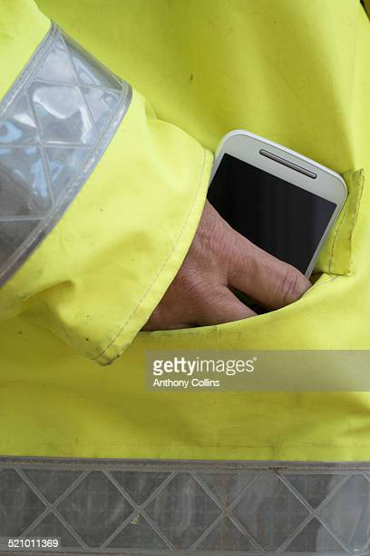 Smartphone in the pocket of a high visibility jacket