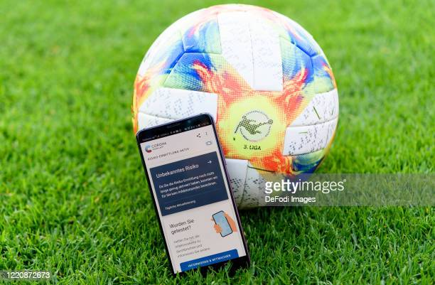 A smartphone is leaning against a play ball with the open Corona Warn app on the screen prior to the 3 Liga match between FC Viktoria Koeln and TSV...