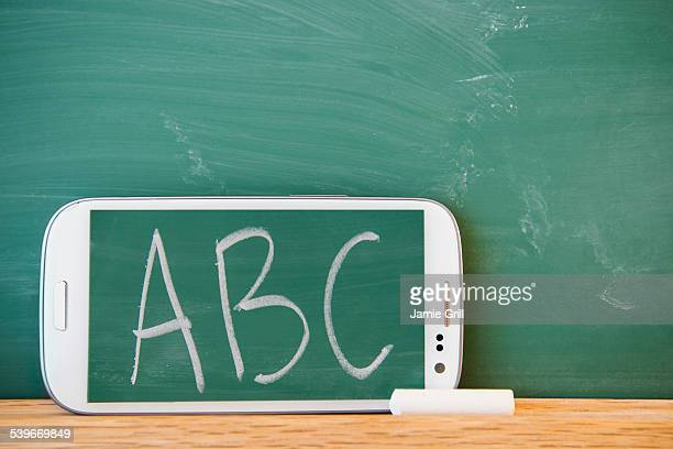 Smartphone leaning against chalkboard with ABC letters displayed