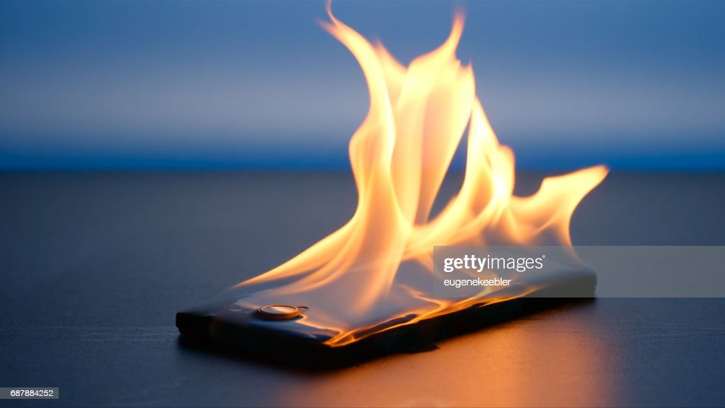 Smartphone lies and burning on a table in the night : Stock Photo