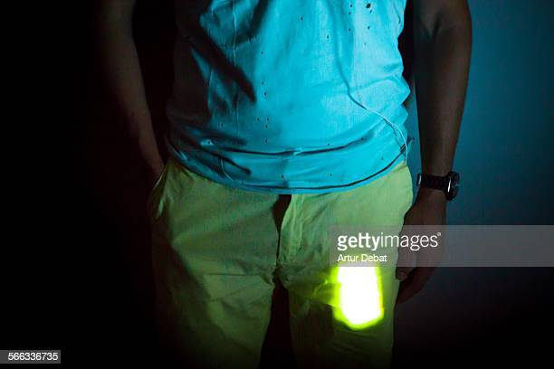 Smartphone lit on pocket of man at night.
