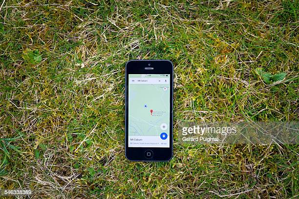 Smartphone lying on the grass in the countryside with a map aplication on