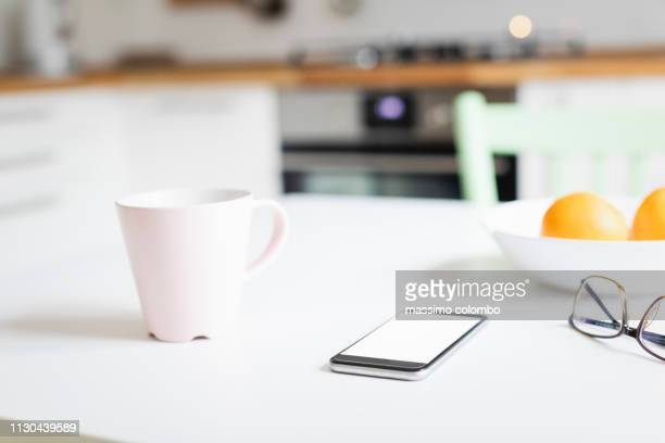 smartphone on the kitchen table - website template stock photos and pictures