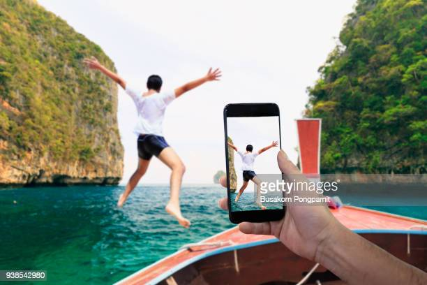 smartphone photographing asian young man jumping from boat into the andaman sea, thailand - tirare la palla foto e immagini stock