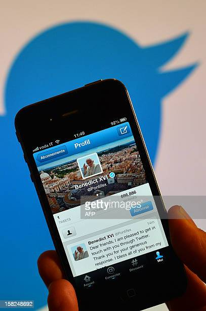 A smartphone showing the first twitter message of Pope Benedict XVI in English is held in front of a computer showing the logo of Twitter on December...