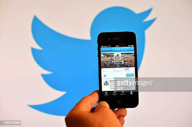 A smartphone showing the first twitter message of Pope Benedict XVI in French is held in front of a computer showing the logo of Twitter on December...