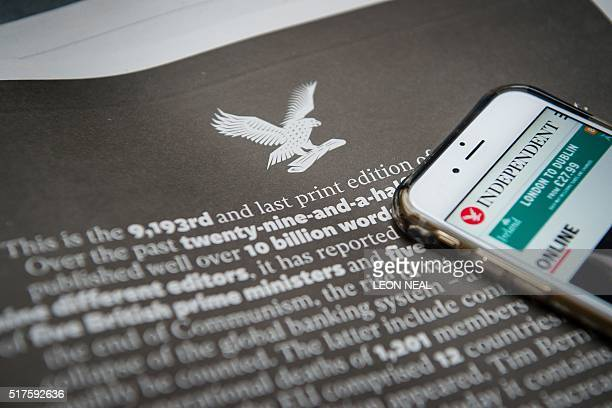 A smartphone showing the online version of the Independent is placed upon a page of the final print edition of the Independent newspaper showing a...