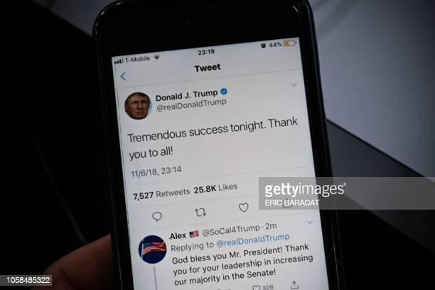 TOPSHOT A smartphone shows a tweet by US President Donald Trump saying Tremendous success tonight after most of the result of the US midterm...