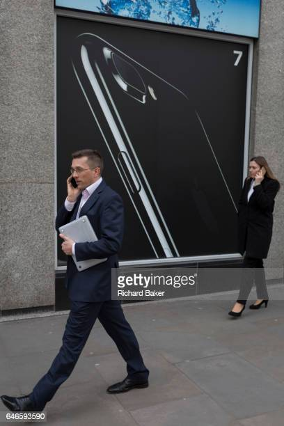 Smartphone users walk past an advert for the Apple iPhone7 on 16th February 2017 in the City of London England