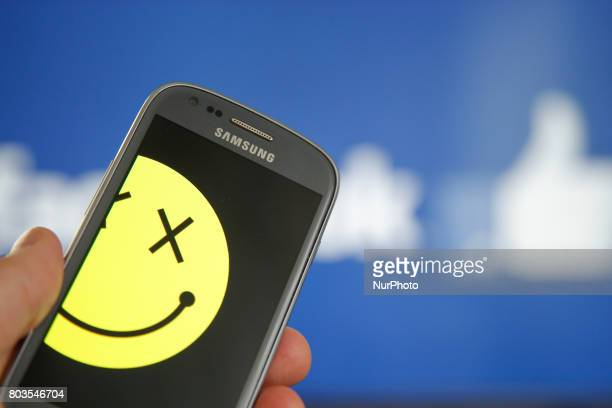 A smartphone with a smiley symbol is seen with the Facebook logo in the background in this photo illustration on 29 June in BydgoszczPoland