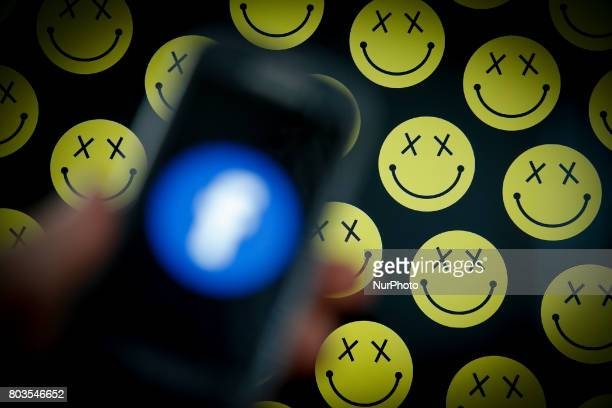 A smartphone with an out of focus Facebook logo is seen with the smiley emoticons in the background in this photo illustration on 29 June in...