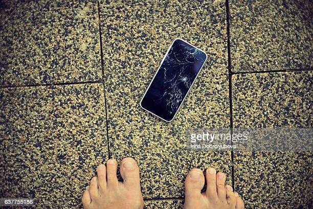 smartphone with broken screen on the ground from personal perspective