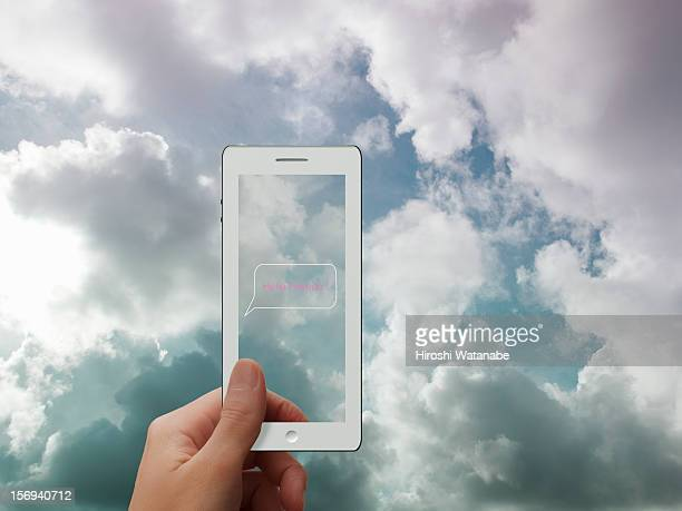 Smartphone with cloudy sky in background