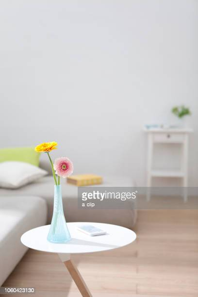 A smartphone with flowers on the side table