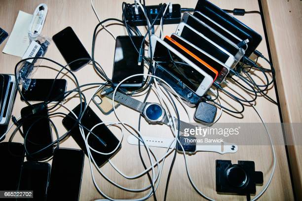 Smartphones and smartwatches charging on desk in high tech office