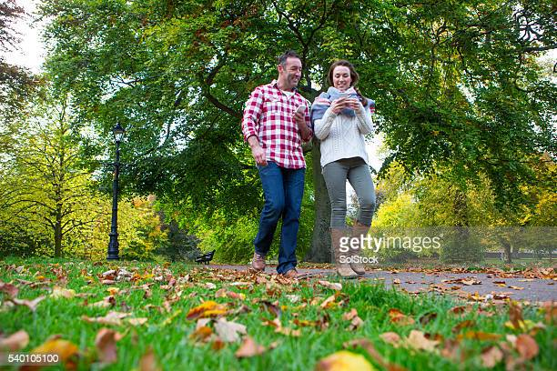Smartphones dominate their walk through the park.