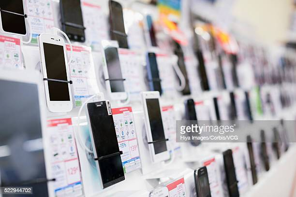 smartphones on retail display - electronics store stock photos and pictures
