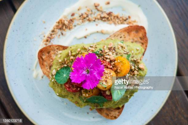 smashed avocado toast. - avocado toast stockfoto's en -beelden