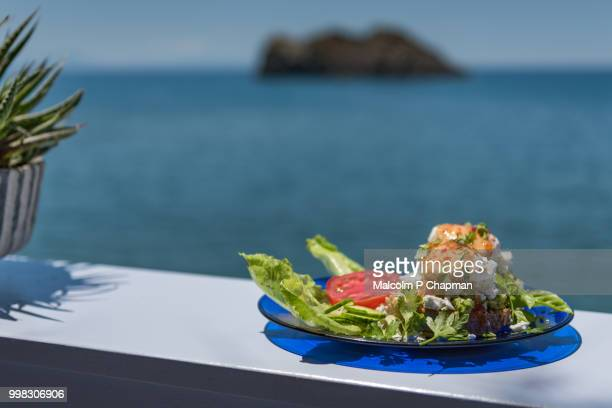 smashed avocado with poached eggs served with crumbled feta cheese and salad, eresos, lesvos, greece - lesbos stock pictures, royalty-free photos & images